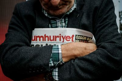 "A man holds a copy of the latest edition of the Turkish daily newspaper ""Cumhuriyet"" during a demonstration outside its headquarters in Istanbul on November 1,2016 a day after its editor in chief was detained by police. .Turkish police detained the editor-in-chief of the opposition newspaper Cumhuriyet, state media reported, while the daily said several of its writers were taken into police custody. Murat Sabuncu was detained while authorities searched for executive board chairman Akin Atalay and writer Guray Oz, the official news agency Anadolu said. / AFP PHOTO / OZAN KOSE"