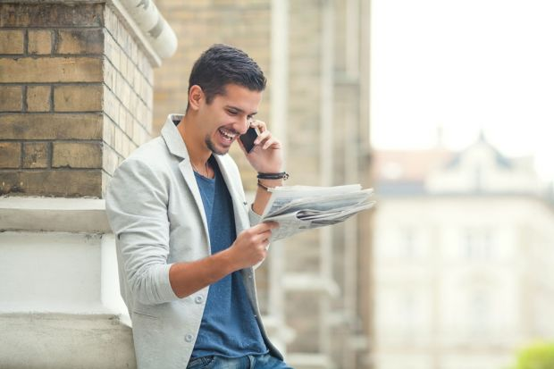 Young businessman reading newspaper and talking on the phone