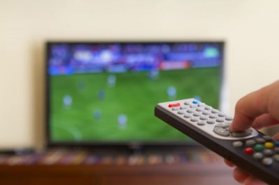 Watching a soccer match in the televison, with a tv remote control in the hand