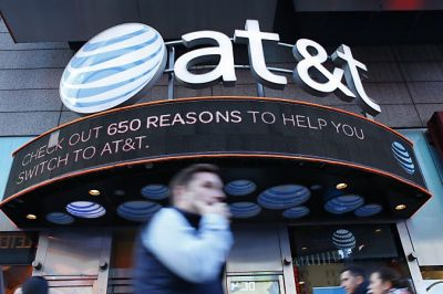 (FILES) In this file photo taken on October 23, 2016 People walk past an AT&T store in New York. .A US judge cleared the AT&T merger with Time Warner with no conditions on June 12, 2018. / AFP PHOTO / KENA BETANCUR