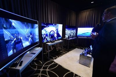 A man views four 4k Ultra HD Tv's from (L to R) Samsung, Panasonic, LG and Sony, on display at The Luxury Technology Show, produced by RAND Luxury in Hollywood, California on September 30, 2015. AFP PHOTO / FREDERIC J. BROWN / AFP PHOTO / FREDERIC J. BROWN