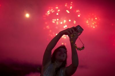 People take photos of fireworks during New Year's celebrations at Copacabana beach in Rio de Janeiro on January 1, 2018. / AFP PHOTO / MAURO PIMENTEL